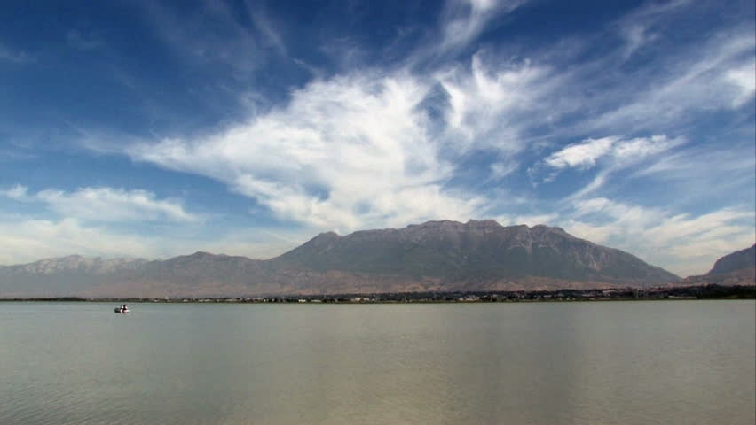 Boat in the distance on Utah Lake near Provo.  Shore line and mountains in distance. Dramatic blue sky and clouds.  - HD stock footage clip