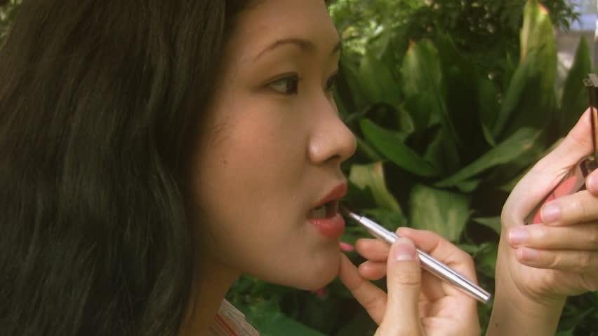 An attractive asian girl applies lip colour. - HD stock video clip