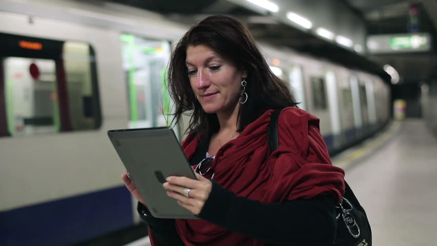 Young woman using tablet computer on subway station