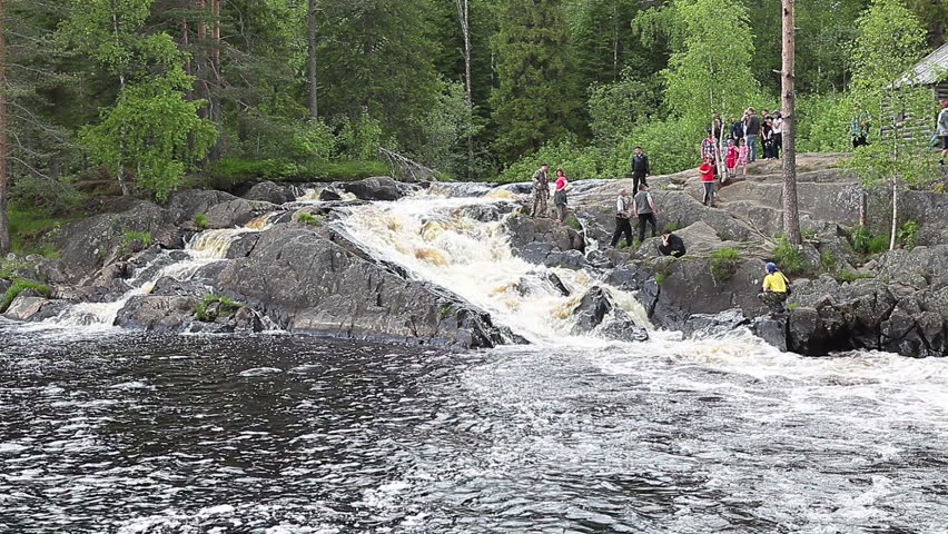 Tourists visit Ruskeala waterfalls - four falls flat in Sortavala region on the river Tohmajoki on circa June, 2012 in Ruskeala, Karelia, Russia - HD stock video clip
