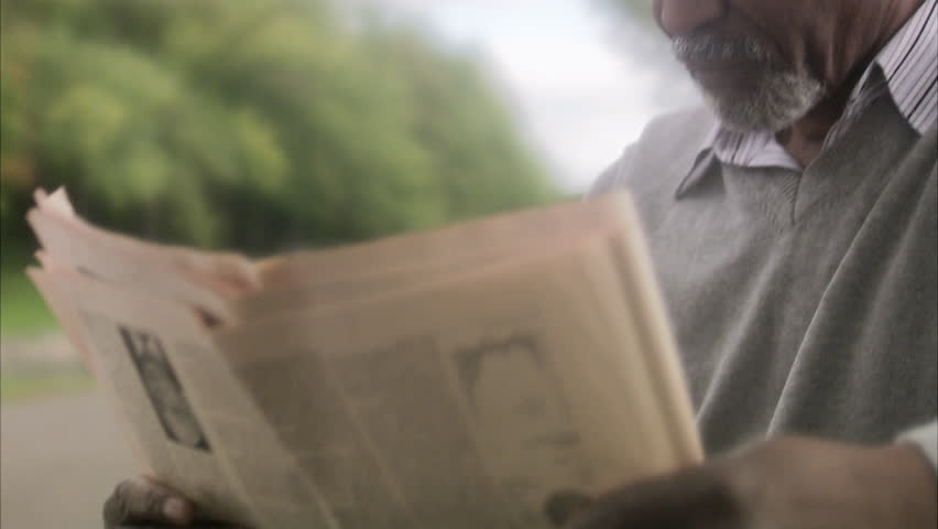 A man sitting on a bench reading a newspaper