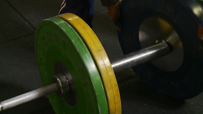 Putting heavy weight plates on a barbell in a gym. - HD stock video clip