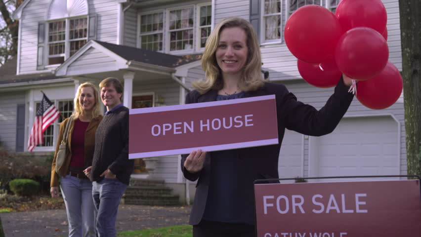 MS, TD, real estate agent holding balloons and a sign saying OPEN HOUSE