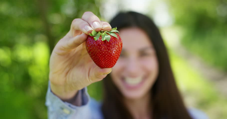 Beautiful young girl holding a clean strawberry in her hand, in the background of nature. Concept: biology, bio products, bio ecology, grow fruits, natural pure and fresh product, diet, healthy. #26641552