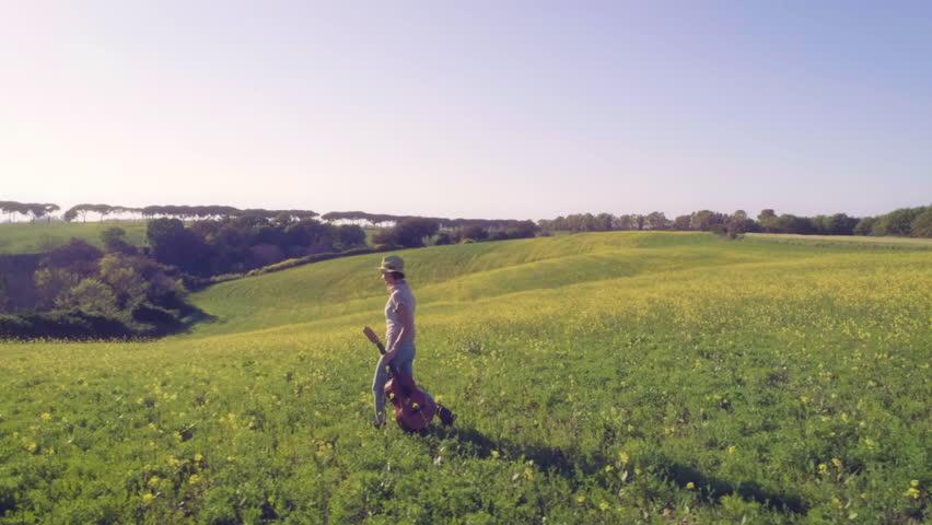 Girl with guitar walks in a green field   Shutterstock HD Video #26939443