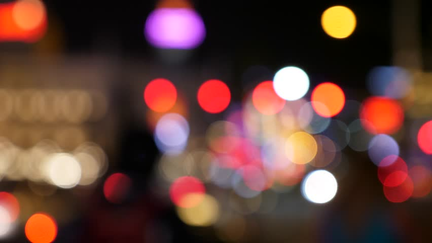 An out of focus shot of people and lights in a busy city at night | Shutterstock HD Video #26965372