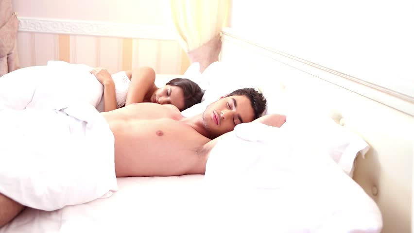 Young adult heterosexual couple waking up in bedroom. dolly shot.
