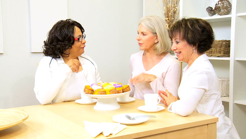 Three mature girlfriends visiting drinking coffee enjoying cakes home - HD stock video clip