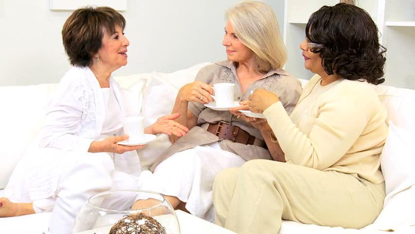 Three senior lady friends enjoying leisure drinking coffee home sofa - HD stock footage clip