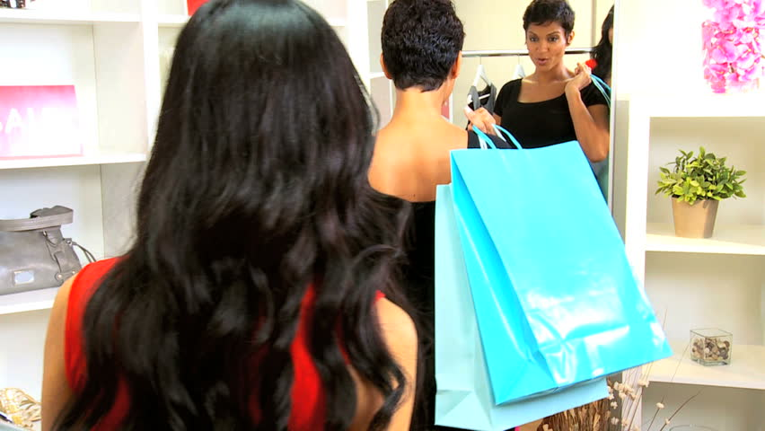 Young multi ethnic girlfriends shopping together in chic designer clothing boutique