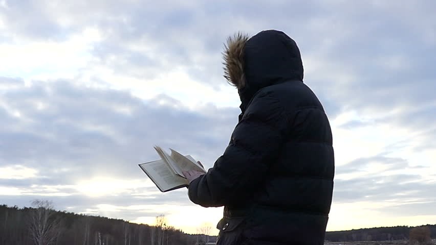 a Man in a Hood Stands With His Back to the Camera and Looks at the Book Against the Blue Sky. the Wind Turns the Pages of the Book. Shooting in Slow Motion. #27009976