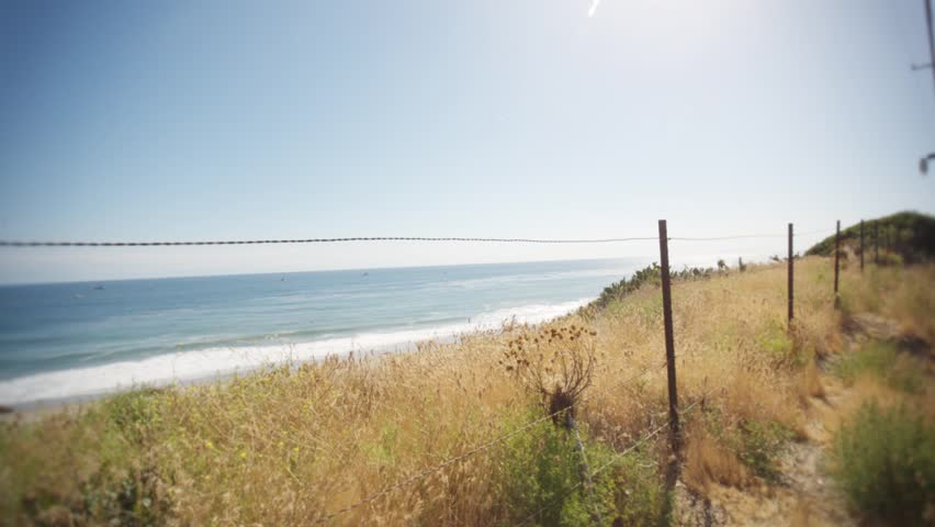 Ocean waves through old metal fence. Scene delivers a roadtrip vibe with a cinematic style at a smooth frame rate. Shot in Malibu -Los Angeles. | Shutterstock HD Video #27021982