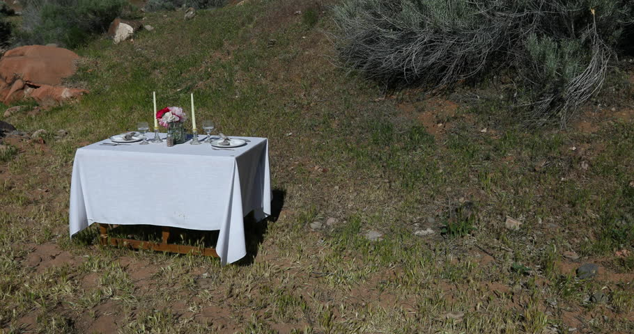 Outdoors formal dining dinner table in nature. Formal table setup in nature for a romantic date with spouse, husband or wife. Plates, white cloth, napkins, flowers, candles and wine glass. | Shutterstock HD Video #27082993