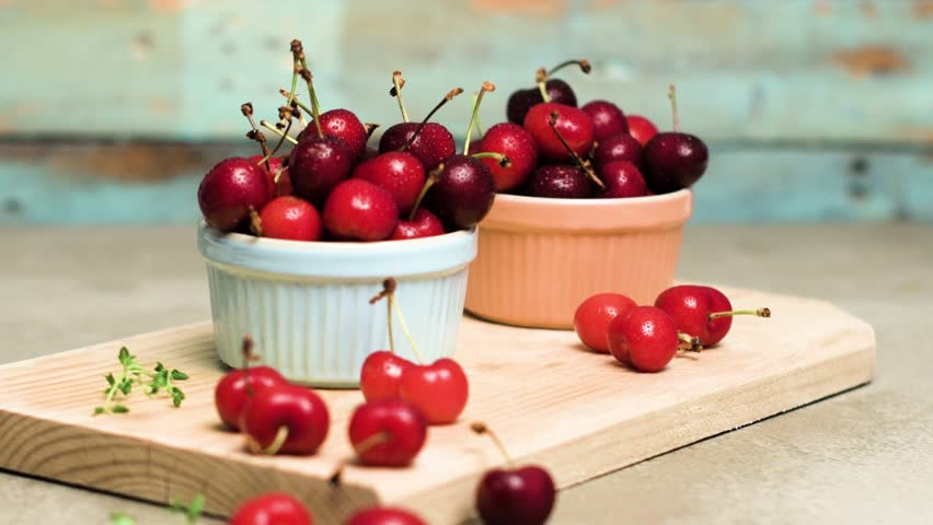 Red ripe cherries in ceramic bowls on kitchen countertop. Rotating slide. #27121576