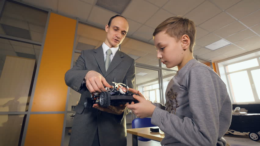 Teacher showing school student eco-friendly future car. Electronic, hydrogen, lithium ion battery car. | Shutterstock HD Video #27197752