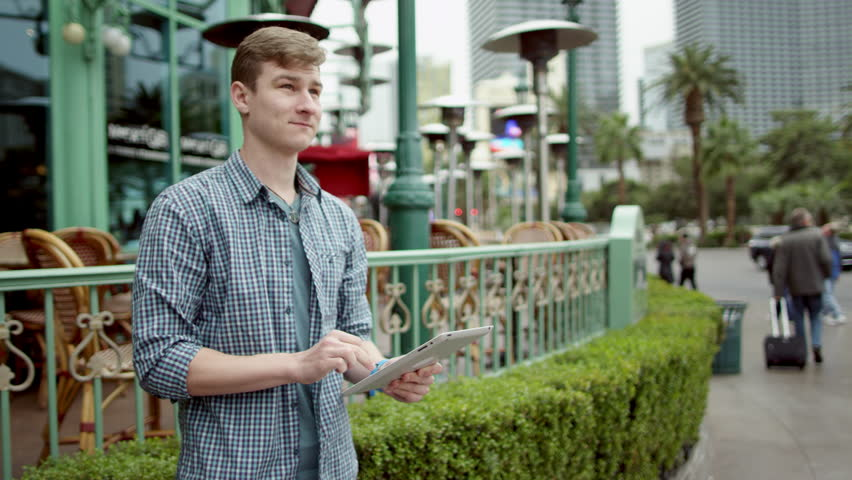 Young man is texting on a street by using his tablet pc | Shutterstock HD Video #27486256