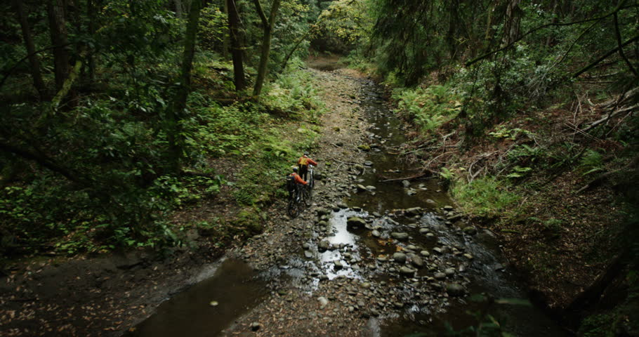 Daytime exterior wide angle crane shot of two men hiking their mountain bikes next to a river in a California rain forest during an adventure race.  #27591502