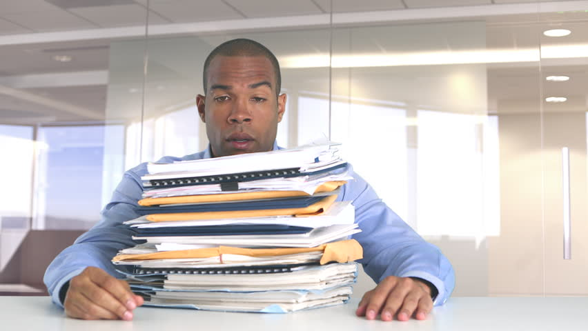 Frustrated businessman at work overwhelmed with work