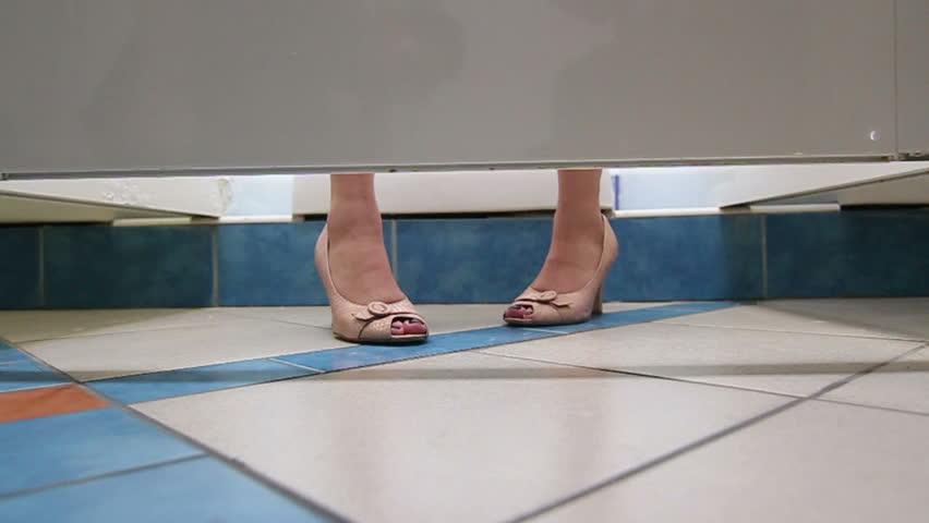 female feet in the bathroom stall