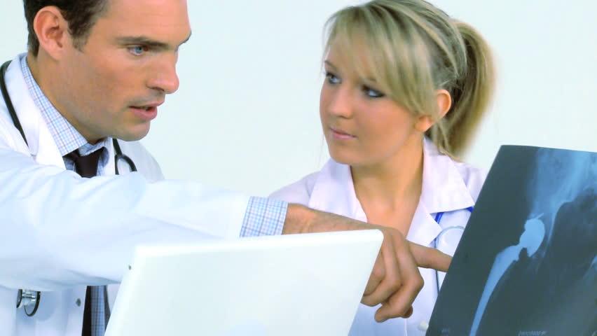 Young doctor & nurse examine patient records - HD stock footage clip