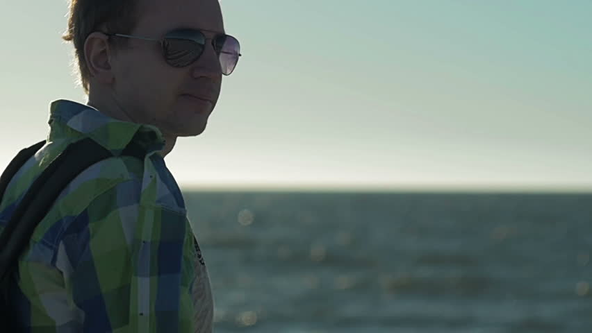 Slow motion, Young man with serious face, turns away from camera in sunglasses against background of sea and blue sky #27854113