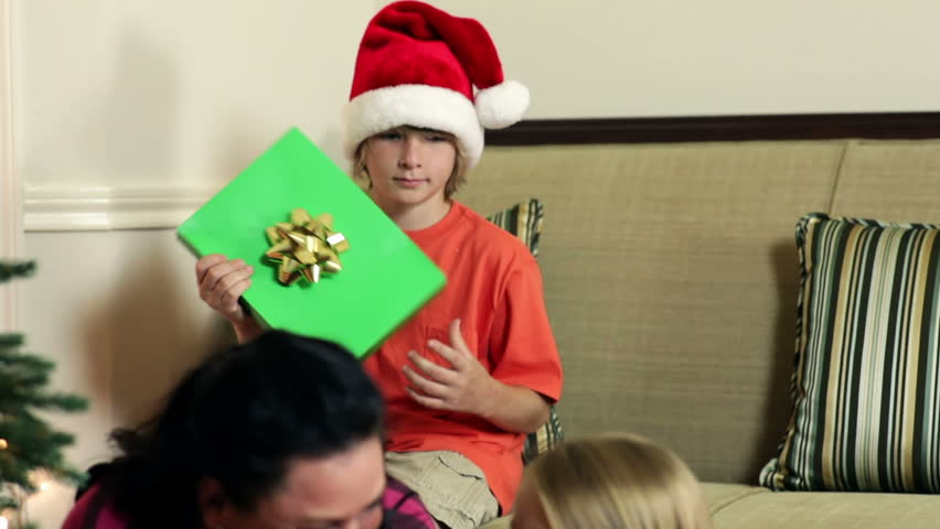 A mother smiles as her little daughter rattles a Christmas gift box to try and guess what is in it. - HD stock video clip