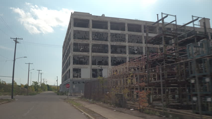 CLOSE UP: Driving towards the ruin of derelict dilapidating Fisher Auto Body Plant 21 in decaying Detroit, United States. The remains of broken down and destroyed car factory in desolate cityscape #28101127
