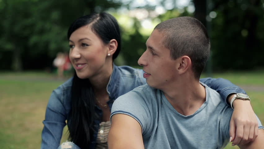 Happy teenage couple in love in the park, steadicam shot
