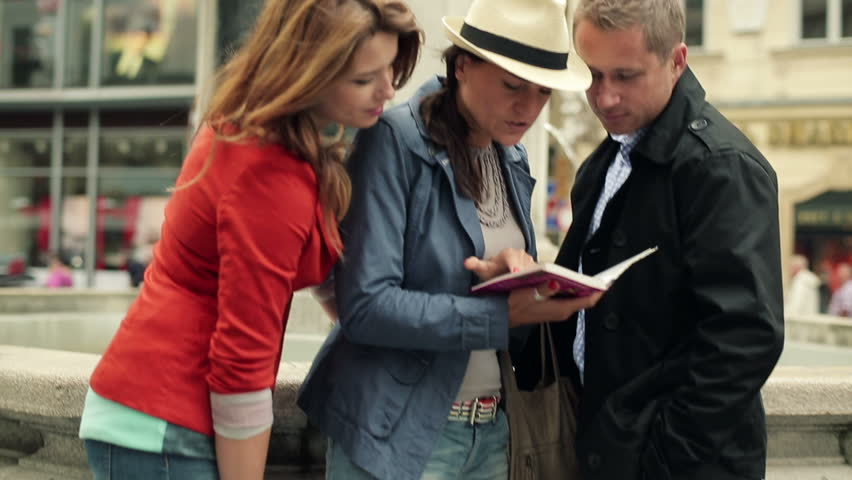 Three friends of tourist looking to guide-book in the city