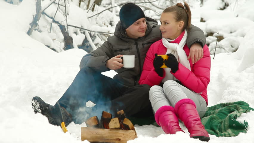 Young couple enjoying winter vacation near bonfire in snowy forest - HD stock footage clip