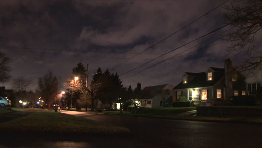 Nighttime in residential neighborhood with cars driving down street arriving
