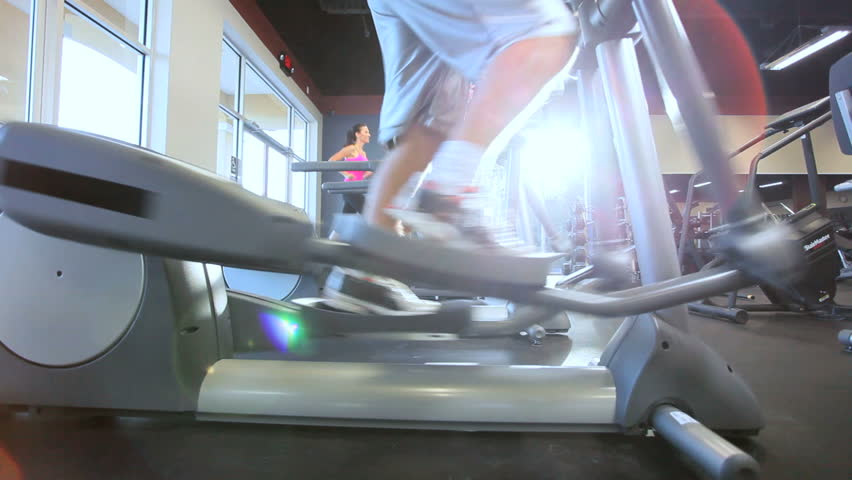 Legs only people working out on cross trainers in modern gym - HD stock footage clip