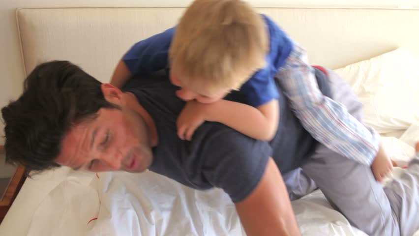Father giving son ride on back before tipping him onto bed. | Shutterstock HD Video #2873038