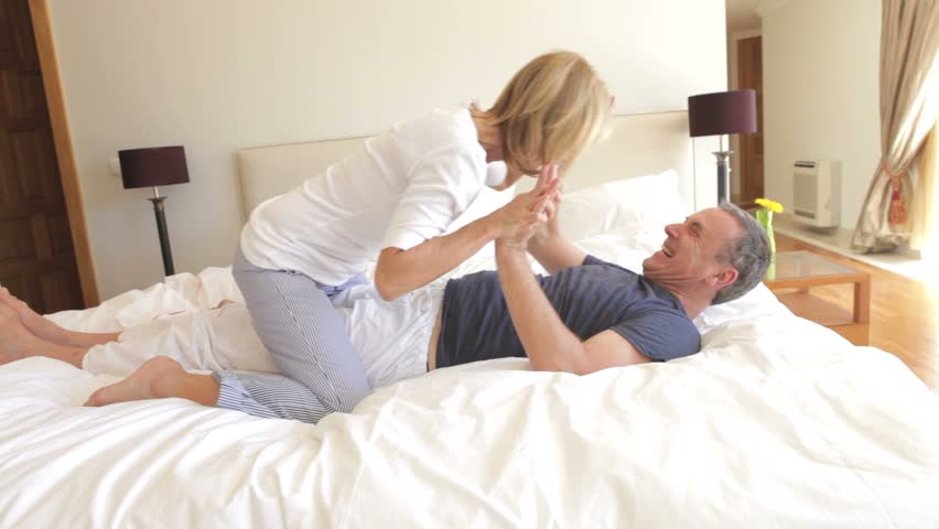 Senior wife sits on husband's chest as they play fight and tickle one another.