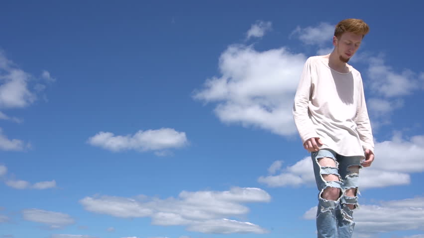 Steadicam shot of a young red haired stilish man against blue sky background. #28753177