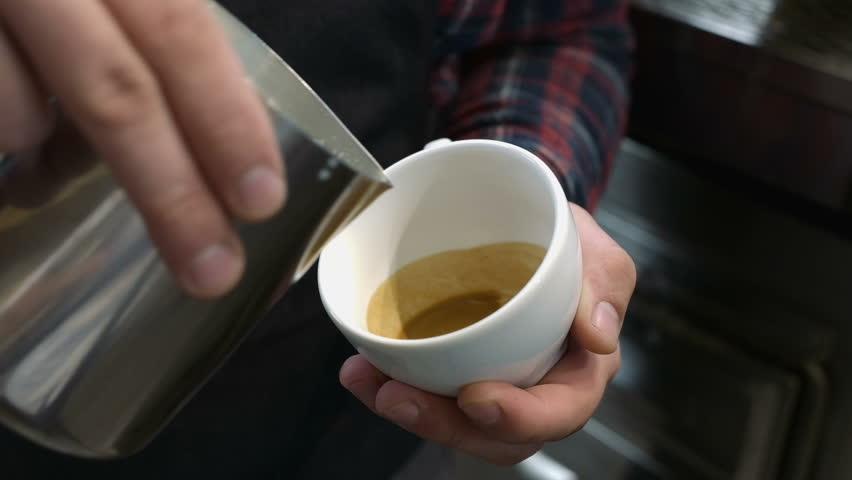 Barista draws milk over a coffee - making latte art for cappuccino | Shutterstock HD Video #28930486