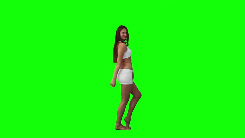 A young smiling woman is posing for the camera against a green background - HD stock footage clip