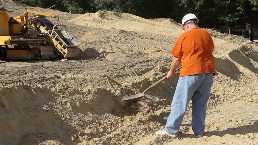 Construction worker uses a spade to dig and move dirt at an excavation site with heavy machinery in the background. - HD stock footage clip