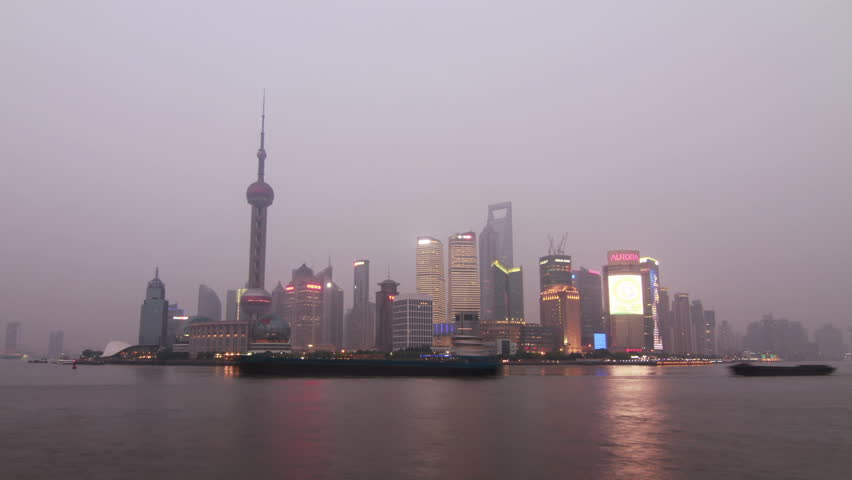 SHANGHAI - CIRCA 2012 - Time lapse from day to night over looking Pou Dong, Shanghai in China circa 2012. Boat moving while skyscrapers are lighting up. Moon is rising behind the skyscrapers.