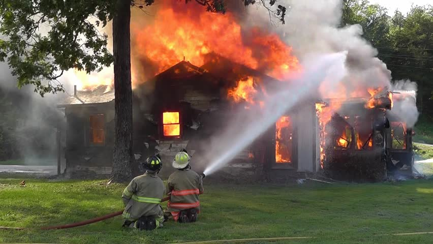 Firemen fight a blazing house fire with water from a high pressure hose in a control burn exercise.