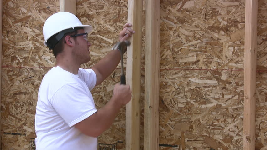 Construction Contractor Working On A New Home Nailing A Stud Wall