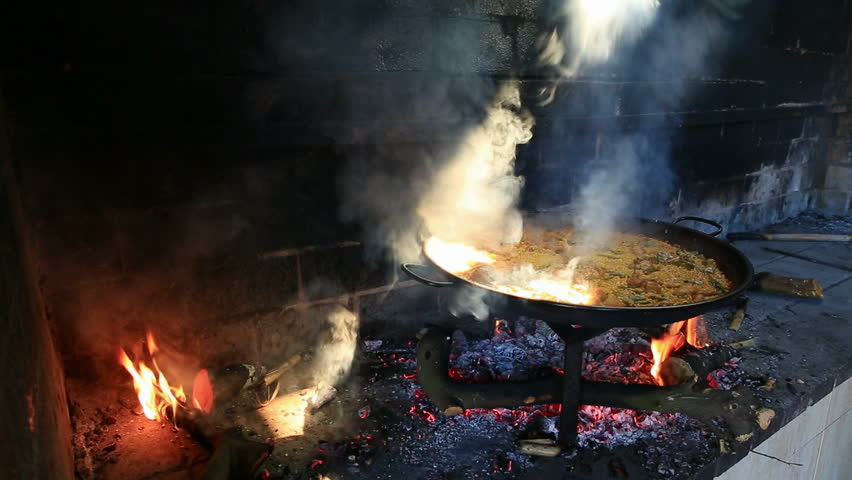 preparing large dish of paella with firewood