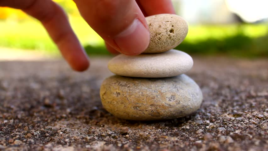 Hand building a stone tower, pile of stones - HD stock footage clip