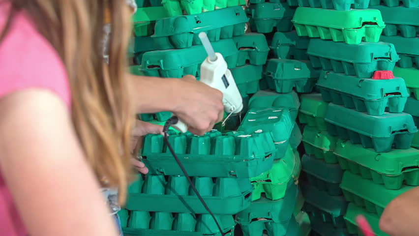 A young boy in school is carefully applying some glue on green egg cartons. They are making something in their art class. | Shutterstock HD Video #29215516