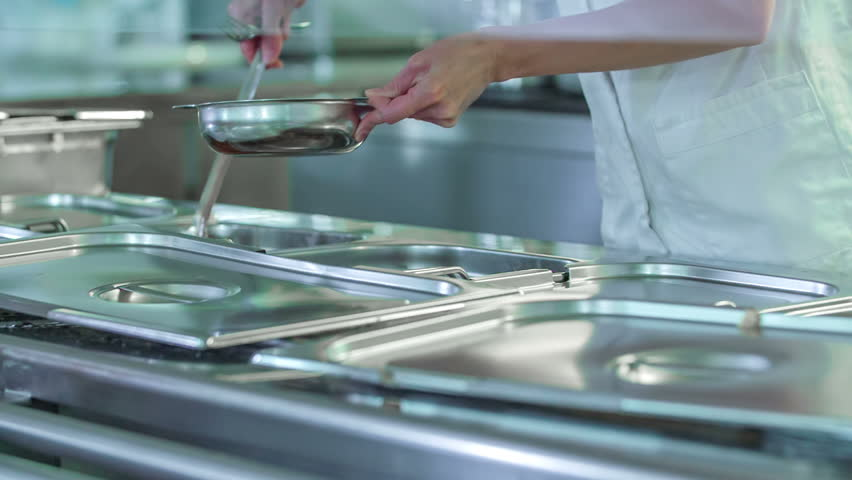 A cook in a school canteen is serving some stew to the students. They are also having a piece of chocolate and strawberry cake for their dessert today. | Shutterstock HD Video #29215525