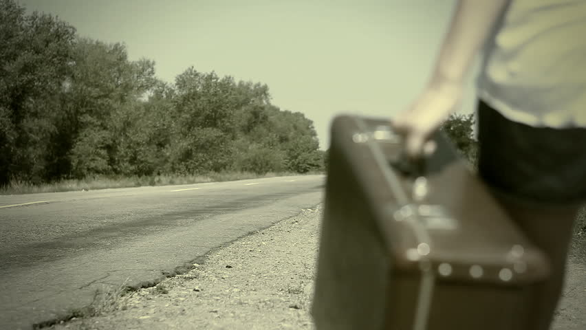 Young woman with guitar on the road and her vintage baggage