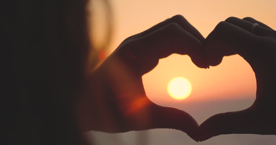 Portrait of a girl from the hands made a heart shape at sunset, on the sea, against an orange background. Concept: love to relax at sea, freedom, love, life style, evening sunset, beach, summer, sun. | Shutterstock HD Video #29525377