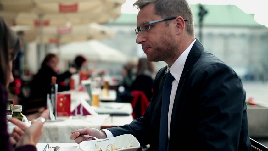 Business people with cellphone eating dinner in the restaurant, outdoor  - HD stock video clip