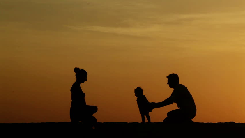 Silhouette of parents teaching their daughter walking