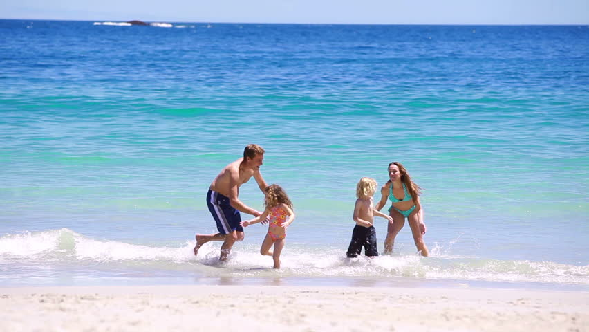 Happy family splashing each other on the beach - HD stock video clip